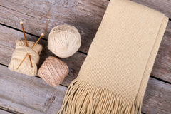 Beige knitted scarf with fringe on wooden background. Stock Photos