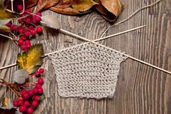 Beige knitting and berries. Knitting beige and red berries on a brown wooden background Royalty Free Stock Images