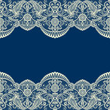 Beige lace border on blue Royalty Free Stock Image