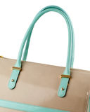 Beige leather handbag with turquoise handles isolated on white. Stock Image