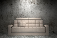 Beige leather sofa in front of grunge wall Stock Images
