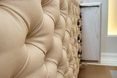 Beige leather upholstery chesterfield style. Close-up. Beige leather upholstery chesterfield style. Wall in the hallway Royalty Free Stock Photo