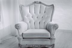 Beige leather wood armchair with golden decor in a white living room royalty free stock images