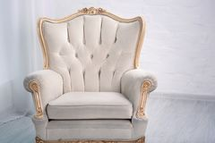 Beige leather wood armchair with golden decor in a white living room stock photos