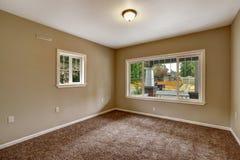 Beige leerer Raum mit braunem Teppichboden Stockfotografie