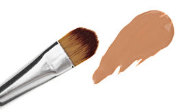 Beige liquid foundation makeup stroke with brush. Isolated on white Royalty Free Stock Photos