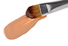 Beige liquid foundation makeup stroke with brush. On white Royalty Free Stock Photography