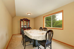 Beige long dining room interior with black table set. Royalty Free Stock Images