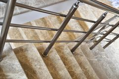 Marble stairs and railings. Beige marble stairs and stainless railings stock image