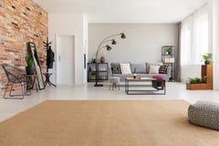 Beige matta i modern vardagsrum som är inre med den gråa soffan, industriell svart metalllampa, träkaffetabell arkivfoto