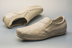 Beige Men`s loafers. Sand summer men`s moccasins on a gray background Royalty Free Stock Image