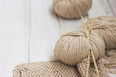 Beige Merino yarn with bamboo needles on white wooden background. Beige Merino yarn with bamboo needles on the white wooden background Royalty Free Stock Image