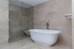 Beige modern luxury bathroom. An elegant looking modern bath tub in a beige bathroom with glass toilet door royalty free stock photos