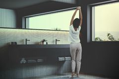 Beige mosaic wall bathroom sink, woman. White mosaic wall bathroom corner with a rug on the floor, a large window, a gray double sink and a long narrow mirror. A royalty free stock images