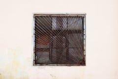 Beige muur met een vierkant venster achter een dikke roestige oude rooster voor achtergrond stock fotografie