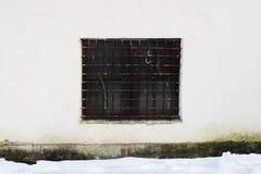 Beige muur met een vierkant venster achter een dikke roestige oude rooster voor achtergrond royalty-vrije stock foto