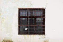 Beige muur met een vierkant venster achter een dikke roestige oude rooster voor achtergrond royalty-vrije stock afbeeldingen