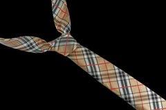 Beige necktie in silk with checkered pattern Stock Images