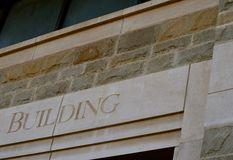 """Beige Office Building. The word """"Building"""" on a beige concrete block building Royalty Free Stock Photography"""