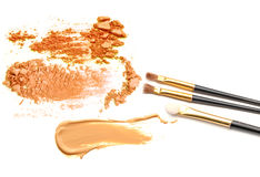 Beige and orange crushed eyeshadow and makeup brush isolated on white background. Royalty Free Stock Images