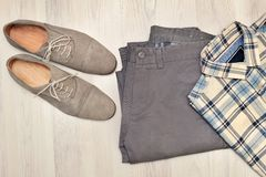Pants, plaid shirt and gray suede shoes. Overhead view of men`s casual outfits on white wooden background. Beige pants, plaid shirt and brown suede shoes Royalty Free Stock Photography