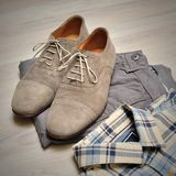 Beige pants, plaid shirt and gray suede shoes. Overhead view of men`s casual outfits. Beige pants, plaid shirt and gray suede shoes. Overhead view of men`s Royalty Free Stock Images