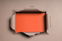 Beige Paper Ripped to Form a Rectangle. Over orange paper in background Royalty Free Stock Images