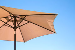 Beige parasol on a blue sky Stock Images