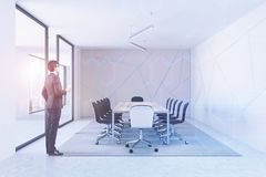Beige pattern meeting room, businessman. Beige pattern boardroom interior with a concrete floor, a long wooden table and black chairs. A businessman. 3d Royalty Free Stock Images