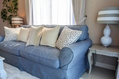 Beige pillows on blue fabric sodfa with lamp in living room. Stock Images
