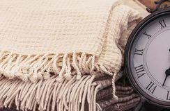 Beige plaid with tassels on the background of the clock stock photo