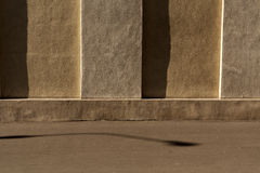 Beige plaster wall and lamp shadow on asphalt. Architectural background and view Stock Photos