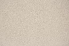 Beige plaster wall texture background. With grainy detail stock photography