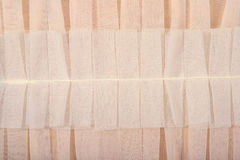 Beige pleated transparent caprone cloth as background texture Royalty Free Stock Images