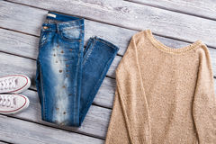 Beige pullover and blue jeans. White canvas shoes and sweatshirt. Casual apparel in outlet shop. Quality items from new collection Royalty Free Stock Photo