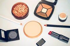Beige pulver, abc-bok, guld- ros och gråa ögonskuggor, guld- rosrouge, eyeliner, kantblyertspenna, röd läppstift Arkivbilder
