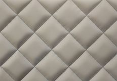 Beige quilted fabric background. Close-up of beige quilted fabric background Royalty Free Stock Images