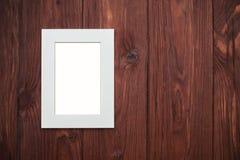 Beige Rahmen ohne Foto auf braunem hölzernem Schreibtisch Stockfotografie