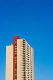 Beige and Red Condo Tower Rising into Blue Sky Stock Photos