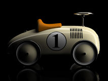 Beige Retro- Spielzeugautonummer eins lokalisiert auf schwarzem Hintergrund Lizenzfreies Stockfoto