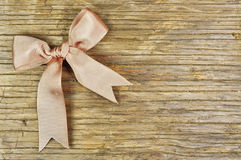 Beige ribbon on a wooden background Stock Images