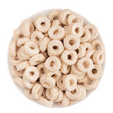 Beige rings corn flakes in white bowl isolated, top view. Cereals. Royalty Free Stock Photo