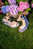 Beige sandals with blue soles lie on the grass. A Stock Photos
