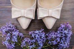 Beige Schuhe mit einer scharfen Nase und Bogen- und Fliederblumen Lizenzfreies Stockbild
