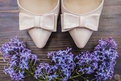 Beige Schuhe mit einer scharfen Nase und Bogen- und Fliederblumen Lizenzfreies Stockfoto