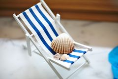 Beige shells of various sizes lie on a little vintage decoration striped beach chair with a blue sea, side view. Beige shells of various sizes lie on a little stock image