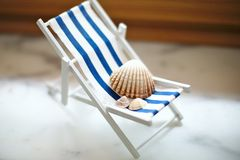 Beige shells of various sizes lie on a little vintage decoration striped beach chair, side view. Beige shells of various sizes lie on a little vintage striped royalty free stock photo