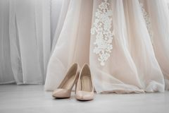 Beige shoes. Wedding Shoes. Bride shoes on heel. The bride`s fees. Wedding decorations stock photography