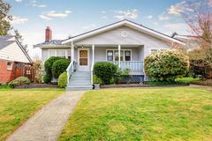 Beige siding house exterior with covered porch and trimmed bushes in front. Royalty Free Stock Images