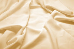 Beige silk fabric. Abstract background, beige silk fabric with waves. Shallow DOF Stock Photo
